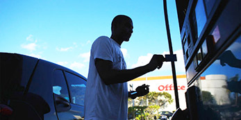 A man at the gas station about to insert his credit card